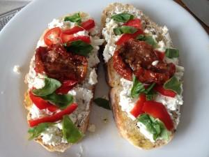 Bruschetta met geitenkaas, paprika, zongedroogde tomaat, honing en verse basilicum
